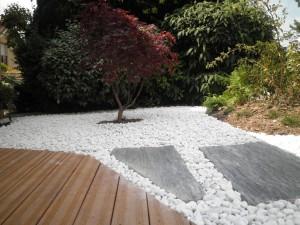 Ambiance minérale entre petit galet blanc et dalle en ardoise. Plancher en bois exotique.