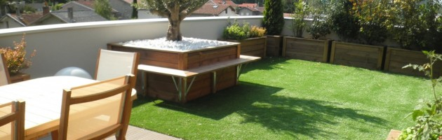 Terrasse composé d'un plancher en composite, de bacs et végétaux et recouvert par du gazon synthétique